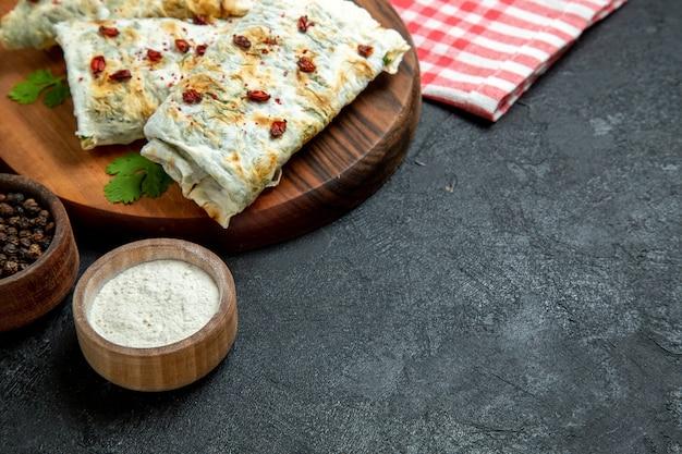 Vue de face de délicieux qutabs avec assaisonnements sur espace gris foncé