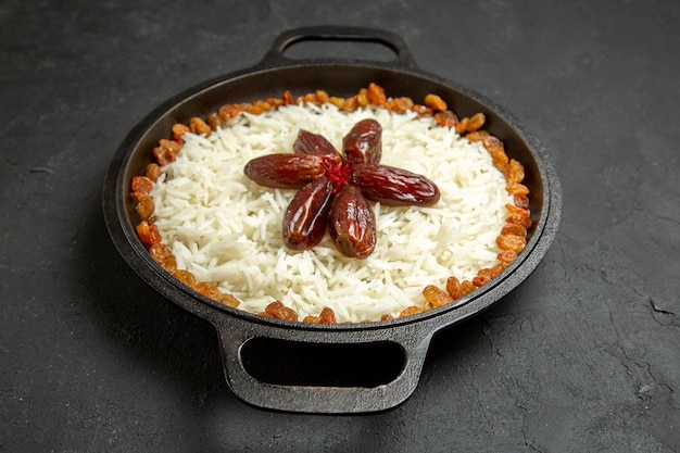 Vue de face délicieux repas de riz cuit plov avec des raisins secs à l'intérieur de la casserole sur la surface sombre riz alimentaire repas oriental dîner