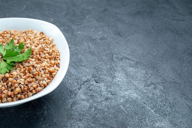 Vue de face délicieux repas utile de sarrasin cuit à l'intérieur de la plaque sur l'espace sombre