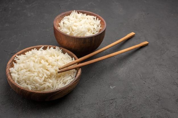 Vue de face délicieux riz cuit plat savoureux repas sur un espace sombre