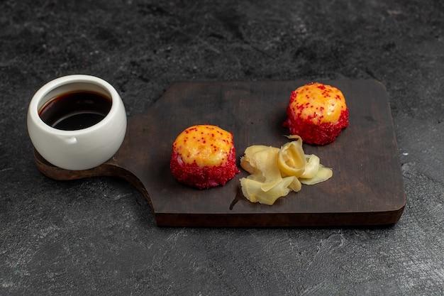 Vue de face de délicieux rouleaux de poisson sushi avec du poisson et des tranches de riz avec sauce sur le mur gris