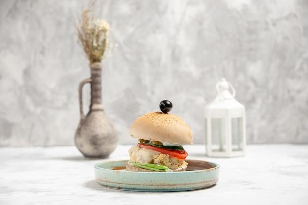 Vue de face d'un délicieux sandwich fait maison avec de l'olive noire sur une assiette et des accessoires sur une surface blanche tachée