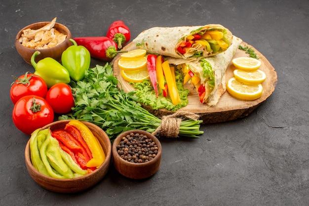 Vue de face délicieux sandwich à la viande de shaurma en tranches avec du citron et des verts sur un espace sombre