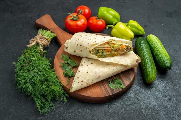 Vue de face de délicieux shaurma en tranches avec des légumes frais sur une surface grise salade burger sandwich repas collation alimentaire