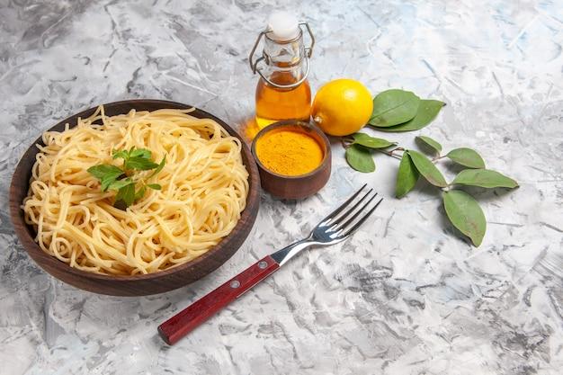 Vue de face de délicieux spaghettis au citron sur un repas de table blanc pâte de pâtes citron
