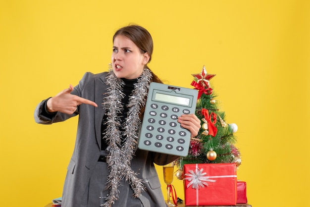Vue de face demandé fille montrant calculatrice debout près de l'arbre de noël et des cadeaux cocktail