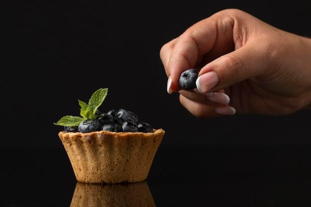 Vue de face des desserts aux myrtilles avec main et menthe