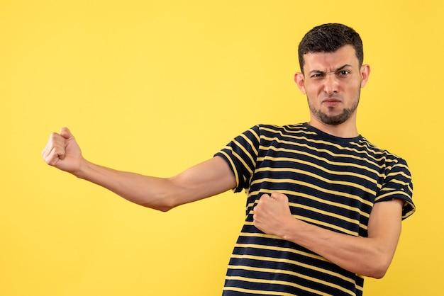 Vue de face déterminé jeune homme en t-shirt rayé noir et blanc fond isolé jaune