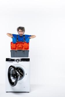 Vue de face déterminé réparateur mettant le sac d'outils sur la machine à laver sur l'espace blanc