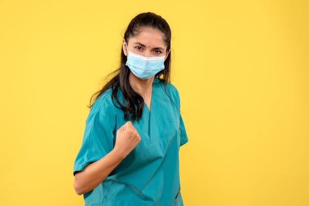 Vue de face déterminée femme médecin montrant son coup de poing sur fond jaune