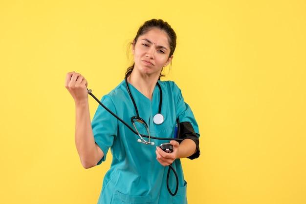 Vue de face déterminée femme médecin en uniforme à l'aide de sphygmomanomètres debout sur fond jaune