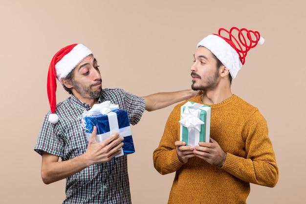 Vue de face deux amis portant des chapeaux de père noël et tenant des cadeaux sur fond isolé beige