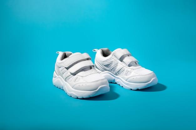Vue de face de deux chaussures de sport pour enfants blanches avec fermetures velcro pour un ferrage facile sur un dos en papier bleu...