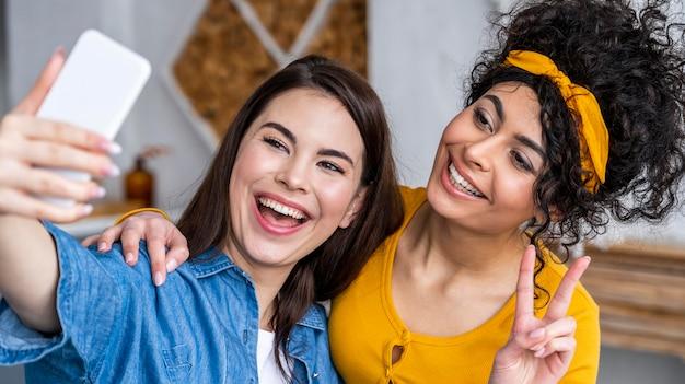 Vue de face de deux femmes heureuses riant et prenant selfie