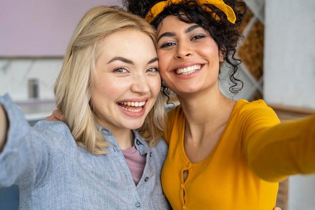Vue de face de deux femmes souriantes prenant un selfie