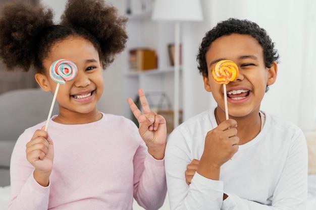 Vue de face de deux frères et sœurs heureux posant avec des sucettes