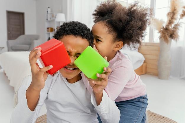 Vue de face de deux frères et sœurs jouant avec des cubes