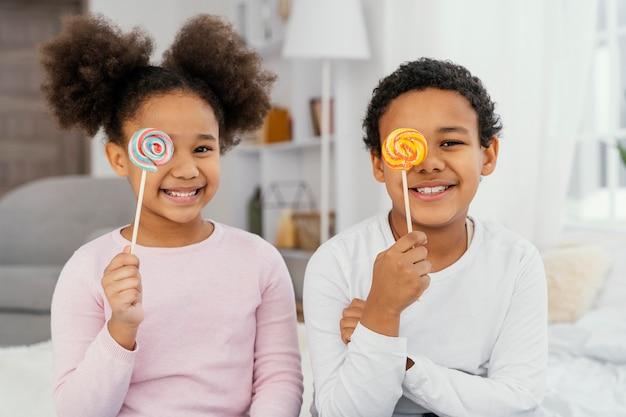 Vue de face de deux frères et sœurs smiley posant avec des sucettes
