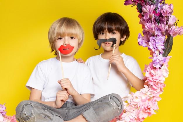 Une vue de face deux garçons adorables doux avec des moustaches assis sur la fleur fait stand sur le sol jaune