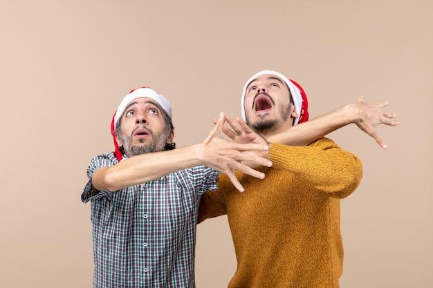 Vue de face deux gars agités avec des chapeaux de père noël à la fois évitant de quelque chose tout en regardant haut sur fond isolé beige