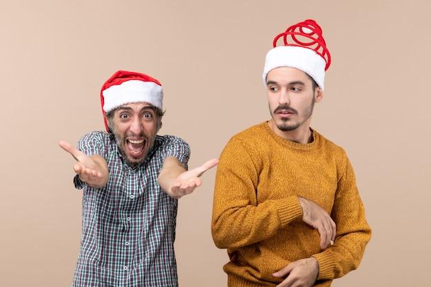 Vue de face deux gars avec des chapeaux de père noël un criant et l'autre déroutant sur fond isolé beige