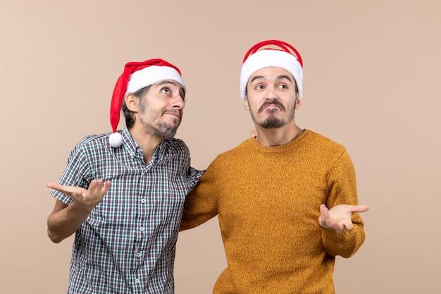 Vue de face deux gars insouciants émotionnels avec des chapeaux de père noël sur fond isolé beige