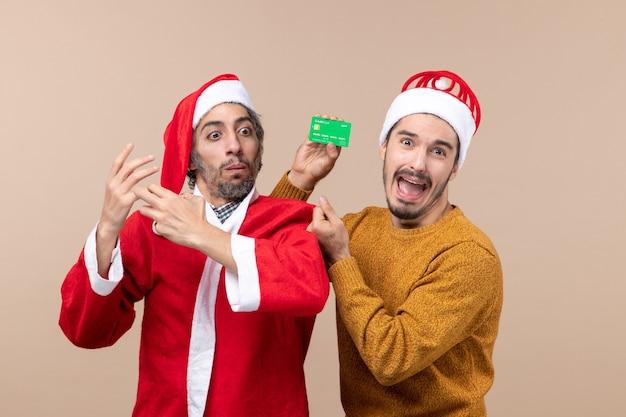 Vue de face deux gars l'un avec manteau de père noël et l'autre avec carte de crédit confus sur fond isolé beige