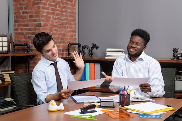 Vue de face deux hommes d'affaires appréciant de travailler ensemble