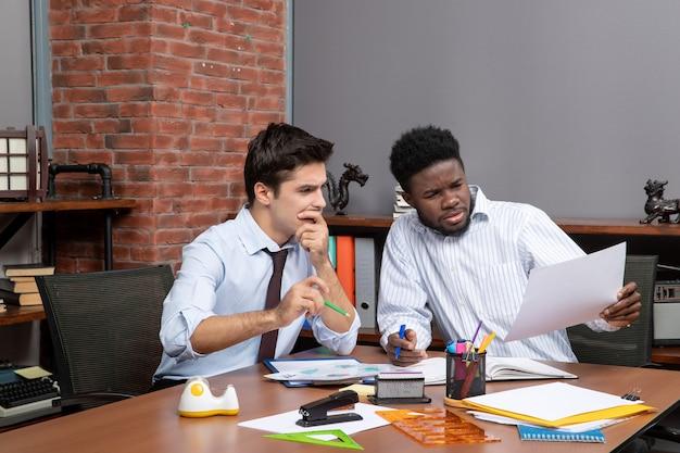 Vue de face deux hommes d'affaires attentifs satisfaisant à travailler ensemble