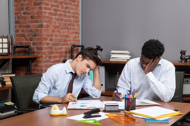 Vue de face deux hommes d'affaires fatigués travaillant ensemble