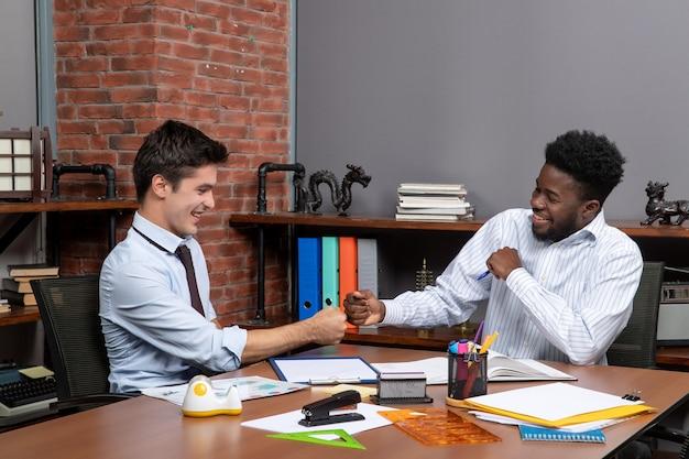 Vue de face deux hommes d'affaires heureux se cognent ensemble