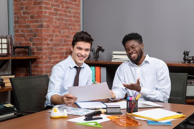 Vue de face deux hommes d'affaires heureux travaillant ensemble des trucs de bureau sur la table