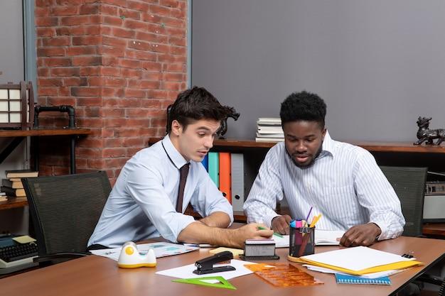 Vue de face deux hommes d'affaires occupés assis au bureau travaillant ensemble