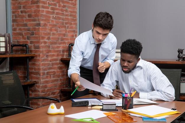 Vue de face deux hommes d'affaires occupés en tenue formelle l'un d'eux montrant du papier à un autre