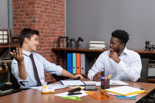 Vue de face deux hommes d'affaires satisfaits assis au bureau travaillant ensemble