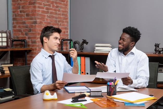 Vue de face deux hommes d'affaires en tenue de soirée travaillant ensemble au bureau photo stock