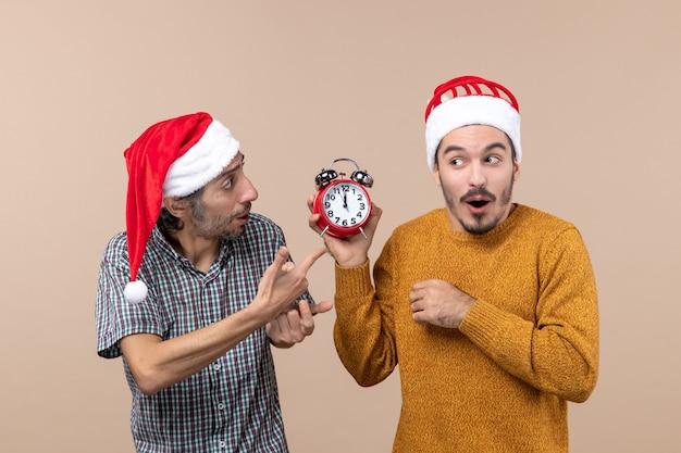 Vue de face deux hommes l'un demandant l'heure et l'autre montrant un réveil sur fond isolé beige