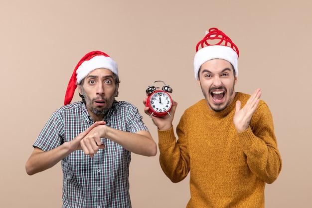 Vue de face deux hommes l'un demandant l'heure et l'autre tenant un réveil sur fond isolé beige