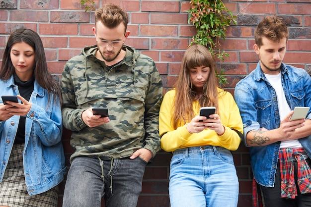 Vue de face de deux jeunes couples avec téléphone portable