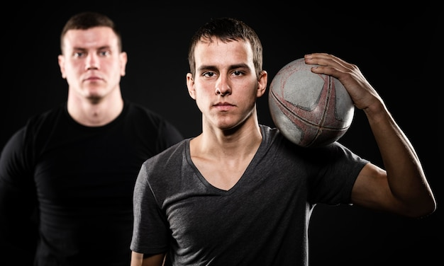 Vue de face de deux joueurs de rugby masculins posant avec ballon