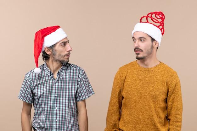 Vue de face deux mecs avec des chapeaux de père noël se regardant sur fond isolé beige