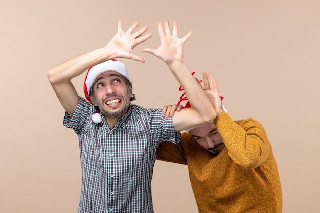 Vue de face deux mecs effrayés avec des chapeaux de père noël à la fois évitant de quelque chose tout en regardant haut sur fond isolé