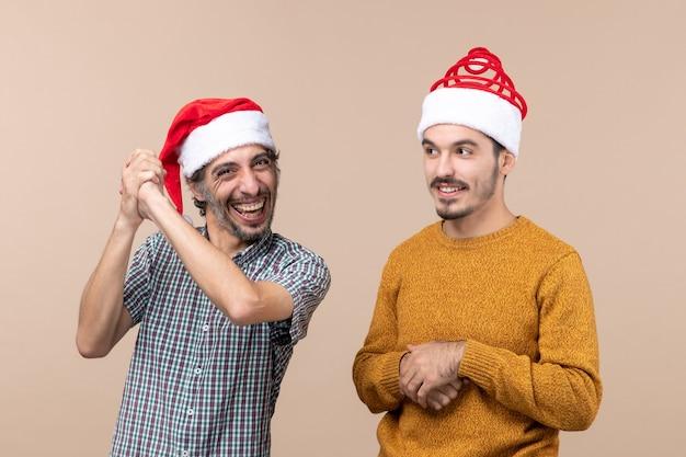 Vue de face deux mecs souriants avec des chapeaux de père noël sur fond isolé beige