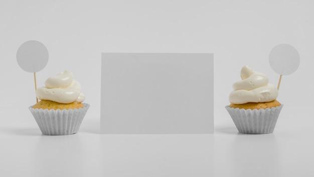 Vue de face de deux petits gâteaux avec carte vierge