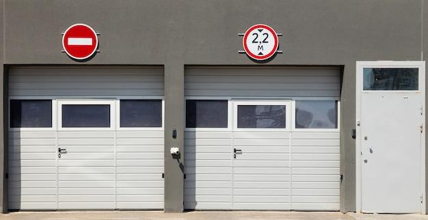 Vue de face à deux portes de garage blanches fermées et une porte d'entrée, murs de moulures grises et panneaux de signalisation dessus