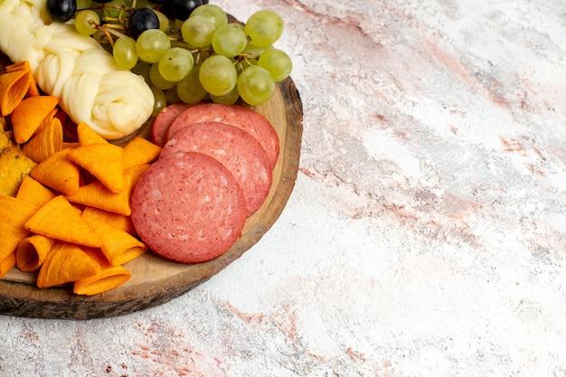Vue de face différentes collations cips saucisses fromage et raisins frais sur espace blanc clair