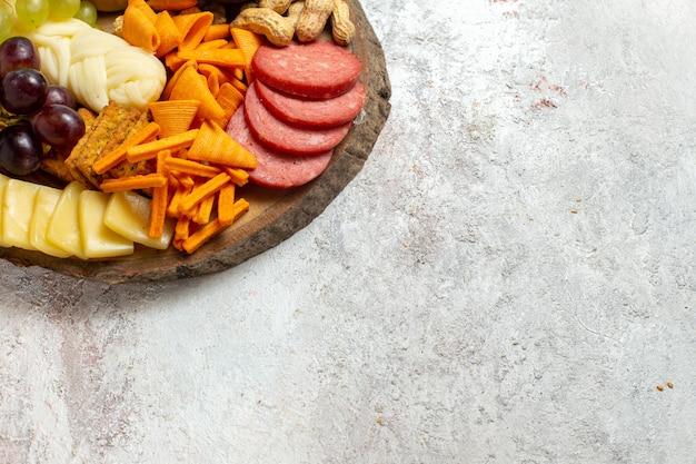 Vue de face différentes collations noix cips fromage et saucisses sur fond blanc noix snack-repas alimentaire