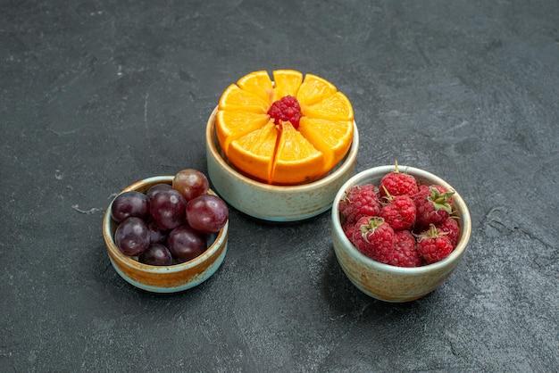 Vue de face différentes composition de fruits frais moelleux et fruits tranchés sur fond sombre fruits frais moelleux santé mûrs