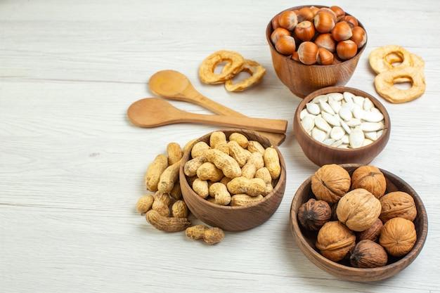 Vue de face différentes noix cacahuètes noisettes et noix sur une surface blanche