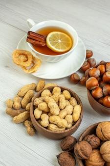 Vue de face différentes noix cacahuètes noisettes et noix avec une tasse de thé sur une surface blanche